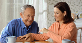 17069-a-woman-and-older-man-sitting-at-a-table-pv